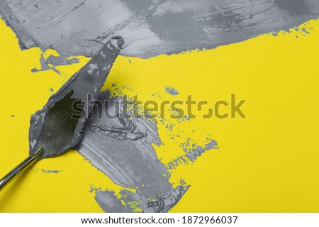 Colors of the year 2021 Ultimate Gray and Illuminating background.  Ultimate gray paint on yellow illuminating background.