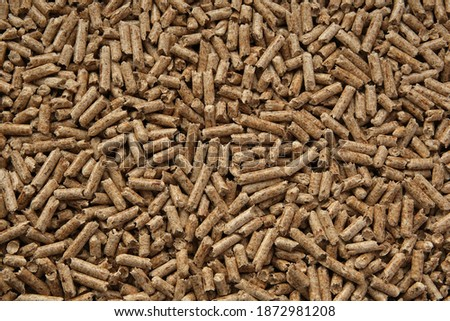 Wood pellets texture. Pellets made from compressed wood and used as natural cat litter. Eco-friendly and biodegradable material. Flat lay image. Royalty-Free Stock Photo #1872981208