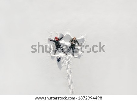 Young couple in love makes snow angels. Snowy white background. Winter, man and woman having fun. Nature parks. Happy girl. Drone, photo from a height.