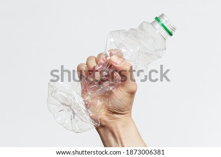 Man smashing a plastic bottle with his hand on white background Royalty-Free Stock Photo #1873006381