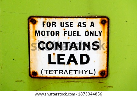 """Leaded gasoline was the primary fuel type produced and sold in America until 1975, as depicted by this sign on an old gas pump (""""contains lead (tetraethyl)).  Royalty-Free Stock Photo #1873044856"""