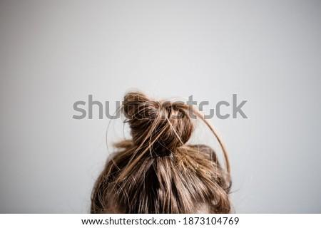 Messy hair bun closeup with grey white background. Royalty-Free Stock Photo #1873104769