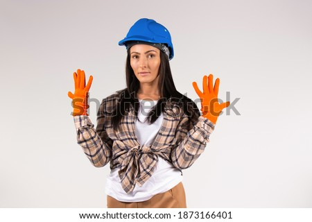 Young handywoman in hard hat and protective gloves posing on white background. Construction and gender stereotypes.