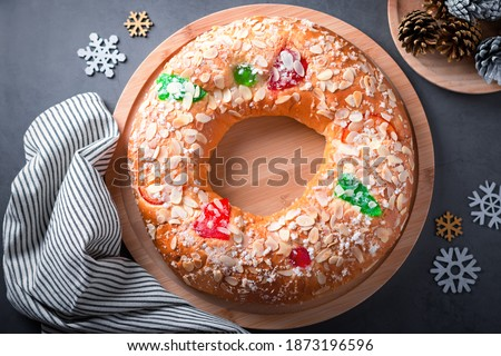 Traditional Epiphany cake Roscon de Reyes on grey stone table top with small Christmas tree and decoration closeup, top view #1873196596