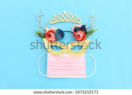 Top view image of masquerade mask background. Flat lay. Purim celebration (jewish carnival holiday). Coronavirus prevention concept, medical mask