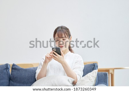 Asian woman using the smartphone on the sofa Royalty-Free Stock Photo #1873260349