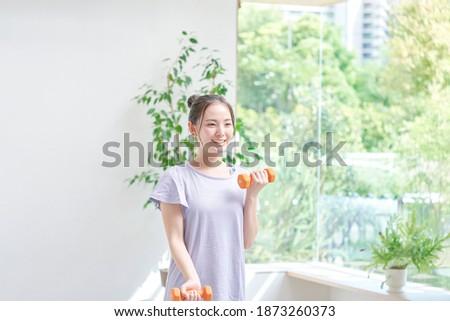 Asian woman exercising at home Royalty-Free Stock Photo #1873260373