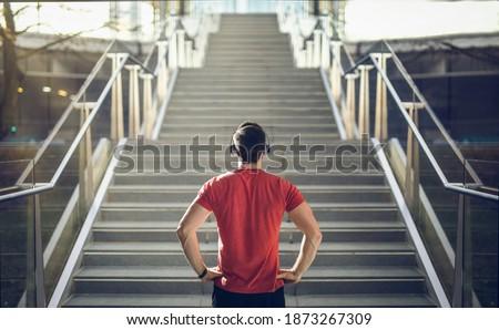Man in red shirt preparing for stair run. Royalty-Free Stock Photo #1873267309