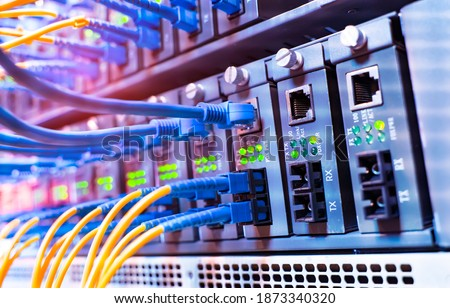 Fiber Optical cables connected to an optic ports and Network cables connected to ethernet ports Royalty-Free Stock Photo #1873340320