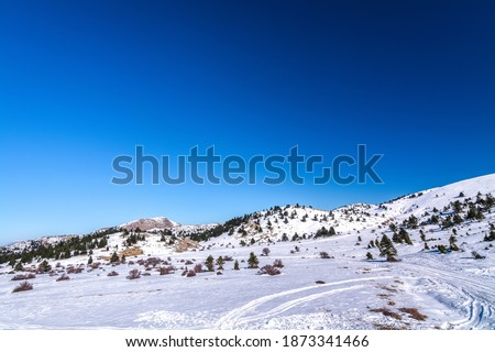 Landscape picture showing a Aroania (Chelmos) mountains area covered with snow near Kalavrita, Greece with blue sky for background. Winter landscape. Winter scene. Snowfall in mountains. Snowy winter  Royalty-Free Stock Photo #1873341466