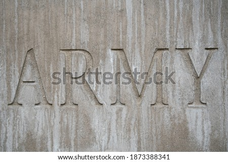"""Text spelling """"ARMY"""" etched into gray cement or concrete, using a serif font. Simple background showing support for the Army or other military forces.  Royalty-Free Stock Photo #1873388341"""