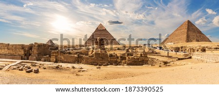 The Sphinx by the Great Pyramids of Egypt near the ruins of a temple in Giza Royalty-Free Stock Photo #1873390525