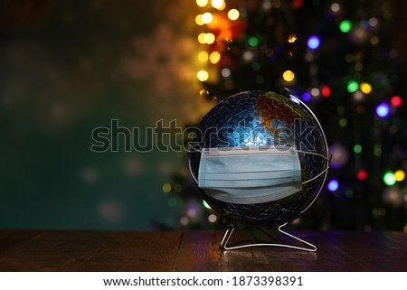 Globe in a medical mask on the background of the Christmas tree