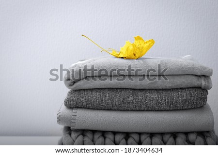 Pantone colors of 2021 - Illuminating Yellow and Ultimate Gray. Crop of stack gray woolen knitted blankets, warm plaids decorated maple leaf, autumn cozy concept