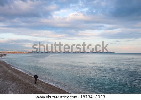 Fisherman walking on the beach of Antalya Taurus mountains and pink purple cloudy sky in the background Royalty-Free Stock Photo #1873418953