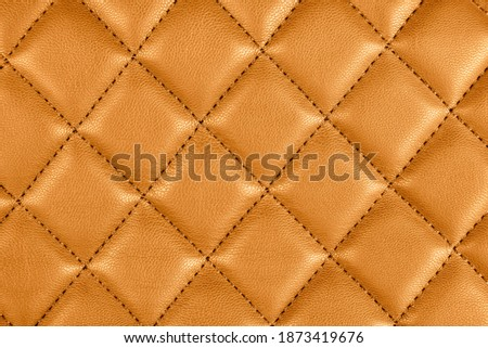 Modern luxury car brown leather interior. Part of perforated leather car seat details. Orange perforated leather texture background. Texture, artificial leather with diagonal stitching.  #1873419676