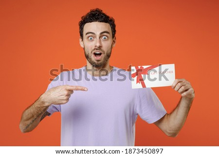 Shocked amazed young man wearing casual basic violet t-shirt standing pointing index finger on gift certificate look camera isolated on bright orange background studio portrait. Tattoo translate fun