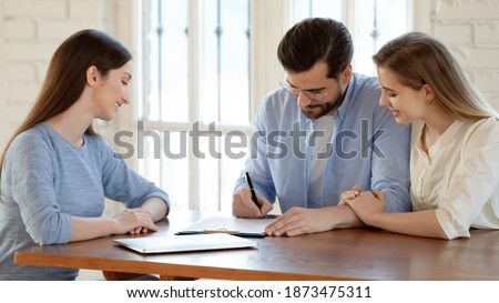 Wide banner view of happy young Caucasian couple sign paperwork close deal with real estate agent. Excited spouse renters put signature on document make agreement with realtor or broker at meeting.
