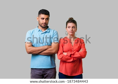 Portrait of upset young couple in casual wear standing together with crossed hands, looking sideways at each other with resentful glance, suspicion. isolated on gray background, indoor studio shot Royalty-Free Stock Photo #1873484443