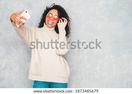 Beautiful black woman with afro curls hairstyle.Smiling model in white trendy sweater.Sexy carefree female posing near gray wall in studio interior.She taking selfie photos for instagram in sunglasses
