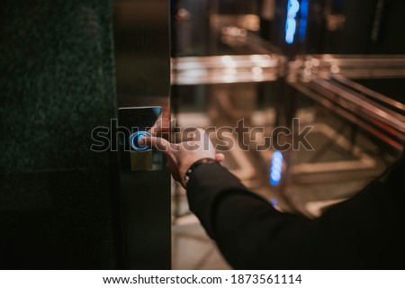 Businessman's finger on the elevator button