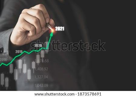 Stock market investment and business growth concept , Businessman writing stock market investment chart with increase green arrow.
