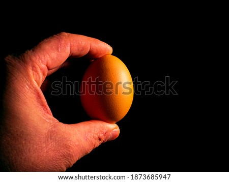 Easter chicken eggs in hand on a black background. Easter chicken eggs. Christ is risen. Christian religion. Religious holiday. Palms of human hands. Christian culture. Religious prayer. Tradition.