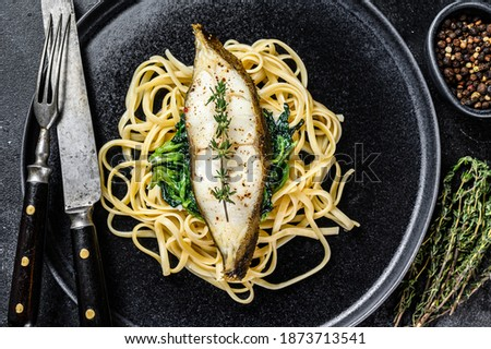 Baked Halibut fish steak and Spaghetti pasta with spinach. Black background. Top view