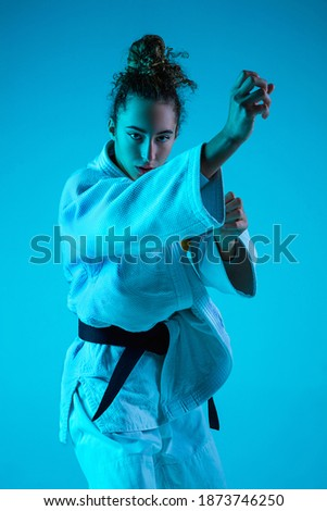 Attack. Professional female judoist in white judo kimono practicing and training isolated on blue neoned studio background. Grace of motion and action. Healthy lifestyle, sport concept Royalty-Free Stock Photo #1873746250
