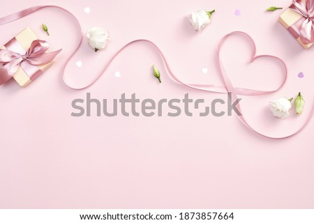 Ribbon in shape of heart with gift boxes and rose flowers on pink background. Happy Valentines day, Mothers day, birthday concept. Romantic flat lay composition.