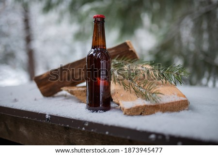 Bottle of beer, wood planks, and pine leaves on a snow-covered table with blurry forest as background. Bottle of alcoholic beverage and snowy pine trees. Winter still life photography Royalty-Free Stock Photo #1873945477