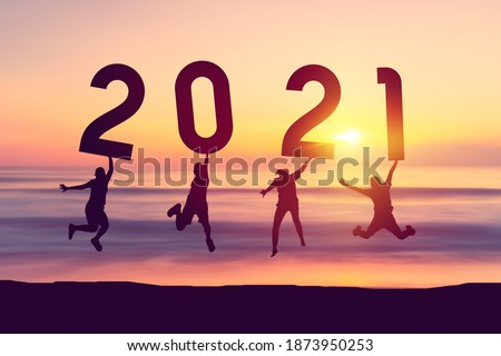 Silhouette friends jumping and holding number 2021 on sunset sky abstract background at tropical beach. Happy new year and holiday celebration concept. Vintage tone color style. Royalty-Free Stock Photo #1873950253