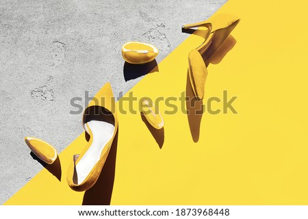Bright illuminating yellow high heel shoes with lemon on yellow and gray color concrete background. Concept of Color of the Year 2021. Top view, flat lay, copy space. Valentine's day  concept. Royalty-Free Stock Photo #1873968448