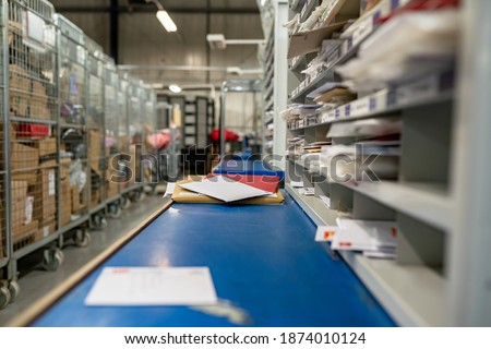 Postal service, post office inside. Letters on a sorting frame, table and shelves in a mail delivery sorting centre.  Royalty-Free Stock Photo #1874010124