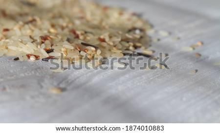 A pile of unboiled fresh rice of various varieties is scattered on the white table. Copy space. #1874010883