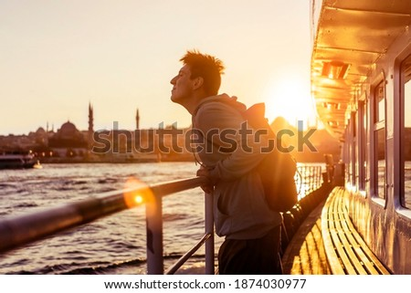 A young travelling man on a ferry floats to the shores of Istanbul, Turkey in the rays of sunset. The beginning of a great adventure. Royalty-Free Stock Photo #1874030977
