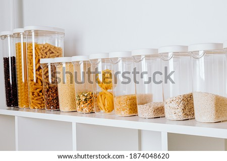 Stocked kitchen pantry with food - pasta, millet, oat flakes, peas, buckwheat, lentils, rice and sugar. The organization and storage in a kitchen in plastic containers. White modern kitchen Royalty-Free Stock Photo #1874048620