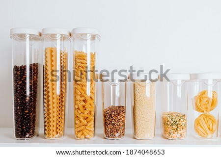 Stocked kitchen pantry with food - pasta, millet, oat flakes, peas, buckwheat, lentils, rice and sugar. The organization and storage in a kitchen in plastic containers. White modern kitchen