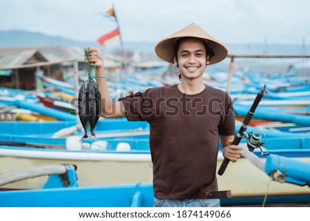 Happy young fisherman on the beach holding his catch fish and shows in front of his boat Royalty-Free Stock Photo #1874149066