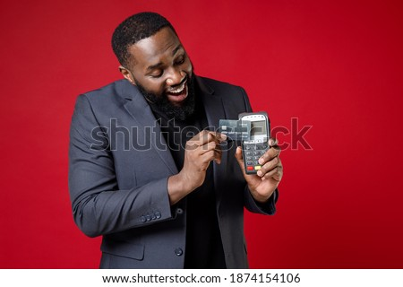 Cheerful young african american business man 20s in classic jacket suit hold wireless modern bank payment terminal to process acquire credit card payments isolated on red background studio portrait Royalty-Free Stock Photo #1874154106