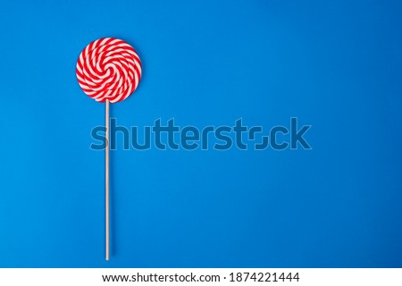 A round Lollipop with a stick in red and white stripes lies on top on a blue background. Sweet round candy of red and white color. Flat bright Lollipop.Christmas candy on a blue background on the left