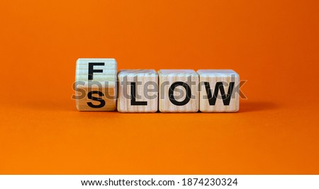 Be slow or in the flow. Turned a cube and changed the word 'slow' to 'flow'. Beautiful orange background, copy space. Business and flow or slow concept. Royalty-Free Stock Photo #1874230324
