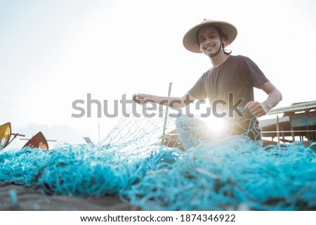 Portrait of a young male fisherman preparing a fishing net Royalty-Free Stock Photo #1874346922