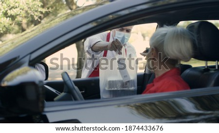 Focus on restaurant worker as he puts this woman's curbside food order through the passenger window of her car.   Royalty-Free Stock Photo #1874433676