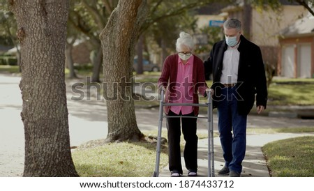 An elderly woman in mask due to the pandemic uses a walker to take a walk outdoors with a friend.  Royalty-Free Stock Photo #1874433712