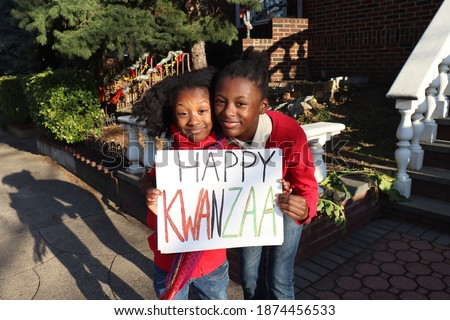 Two black kids holding Happy Kwanzaa outside urban home