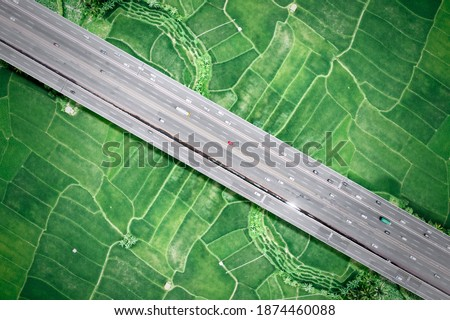 Beautiful aerial view of traffic on elevated road and tollway surrounded green rice fields in Jakarta city, Indonesia Royalty-Free Stock Photo #1874460088