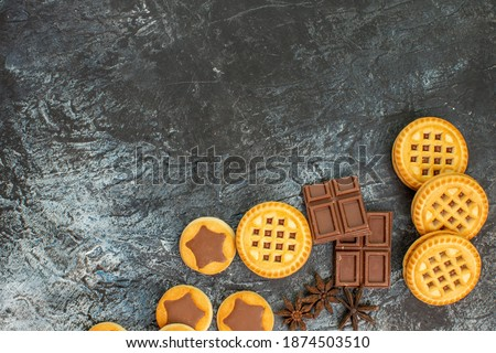 close up view of sweet cookies with chocolate bars on the right side of grey background #1874503510