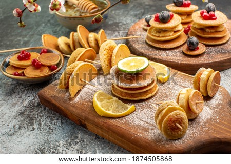 Top view of stuffy pancakes on cutting board and honey on the gray background Royalty-Free Stock Photo #1874505868