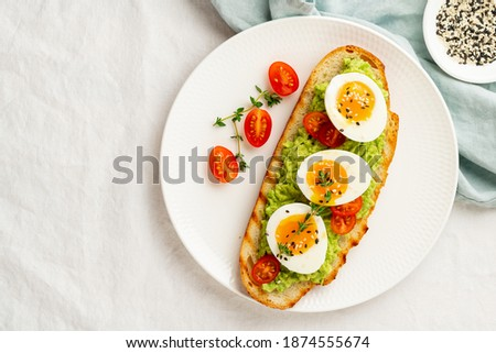 Avocado toast with toasted bread soft-boiled eggs with yellow yolk and tomatoes with herbs on white plate on light tablecloth Royalty-Free Stock Photo #1874555674